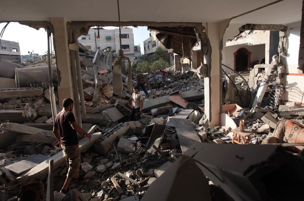 Palestinians inspects  house which police said was destroyed in an Israeli air strike in Jabaliya
