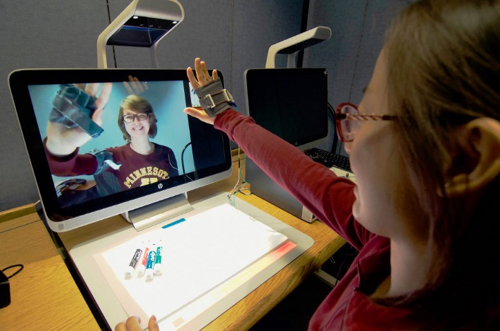 A woman raises her hand towards a webcam during a videochat with a friend. Her hand is encased in a cloth device with shape memory alloy springs.