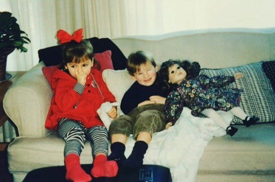 little girl and boy on a couch next to a large doll