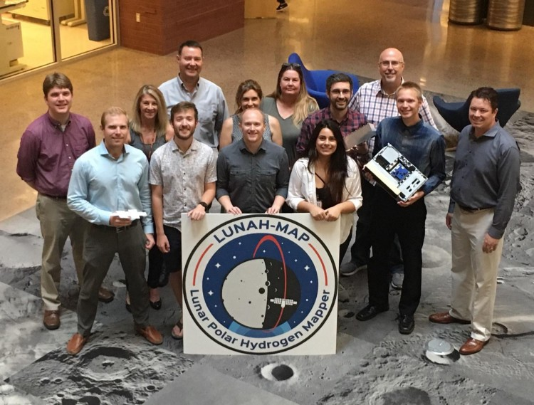 This image shows the LunaH-Map team standing with a large poster of the LunaH-Map logo.