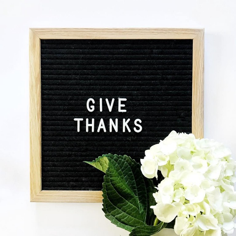 """a black letter board with a wooden frame holds the words that spell """"Give Thanks"""" with a pretty white flower in the corner."""