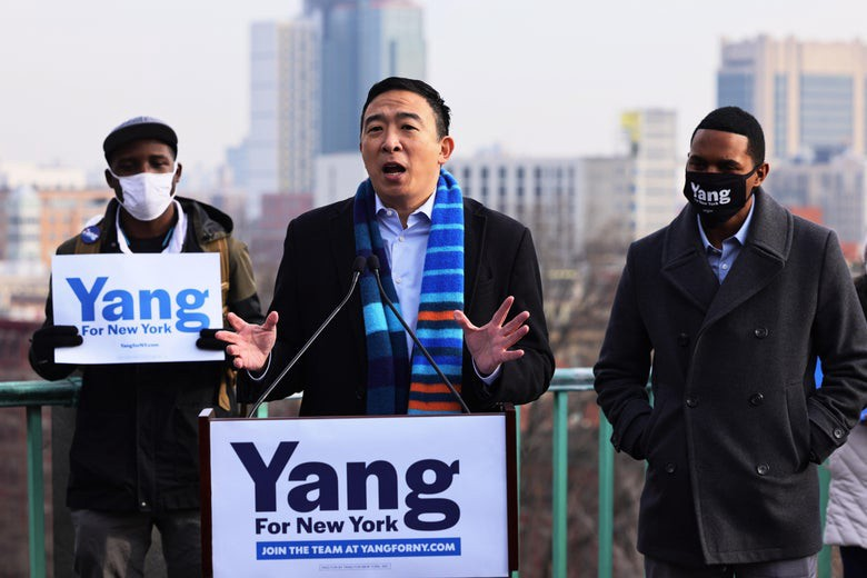 Andrew Yang stands at podium giving a speech for mayoral race.