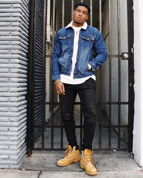 Black man with earrings and crisp cut hair wearing a blue jean jacket layered on top of a white T-shirt. Accessories: light colored metal bracelet and white ring. Brown timberland boots and dark pants.