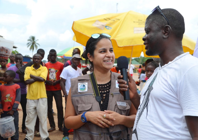 A young Liberian male stands holding a microphone, in conversation with a white female wearing a brown vest. Behind them is a market scene with a group of young Liberian men gathered to watch.