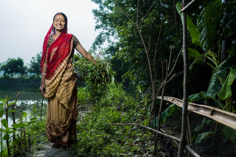 A smiling woman wearing brightly colored clothing stands next to a small plant and a small body of water in Bangladesh.