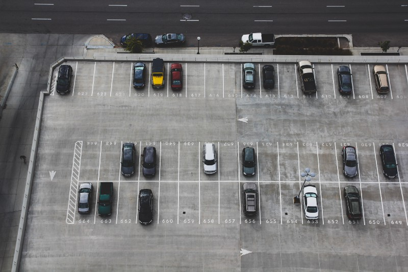 Arial view of a grey parking lot and a few cars