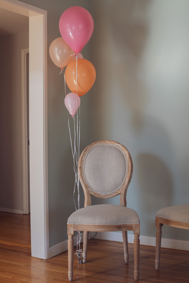 An empty chair with colorful balloons-- denoting someone is absent.