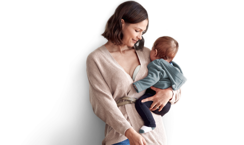 Example of a successful digital health product. A woman carrying a baby while using an Elvie pump.