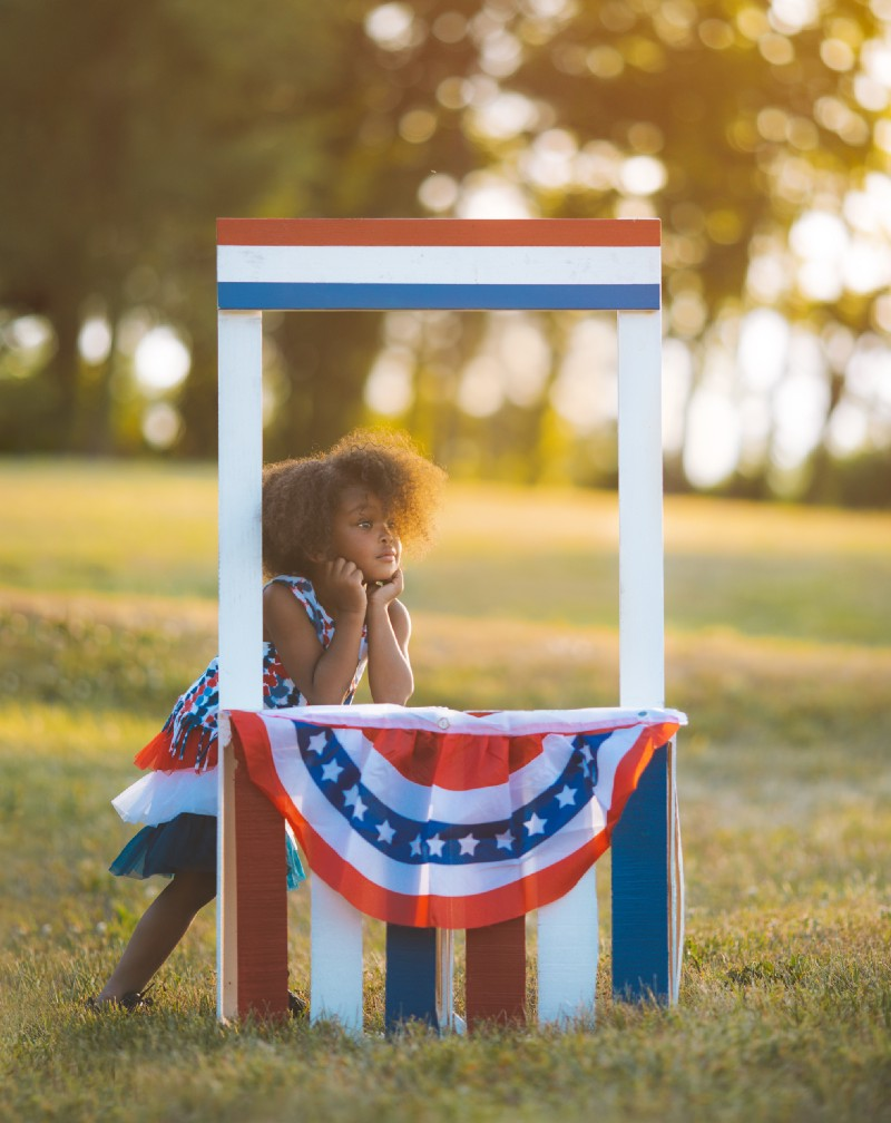 Cute little girl with a lemonade stand dressed up with the American flag