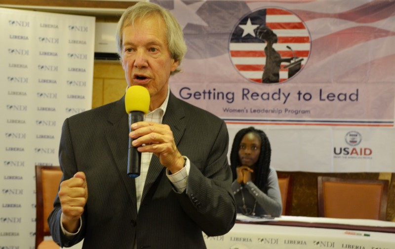 "A white man holds a microphone, speaking to an audience not seen in the photo. Behind him is a banner that reads ""NDI Liberia"""