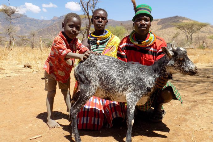Two men and a small child, dressed in brightly colored clothing, kneel behind a black and white goat. Behind them is a dry, dirt field.