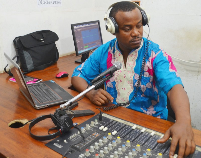 A Liberian male in bright clothing sits at a table in front of a sound mixer, microphone and laptop computer. He wears headphones.