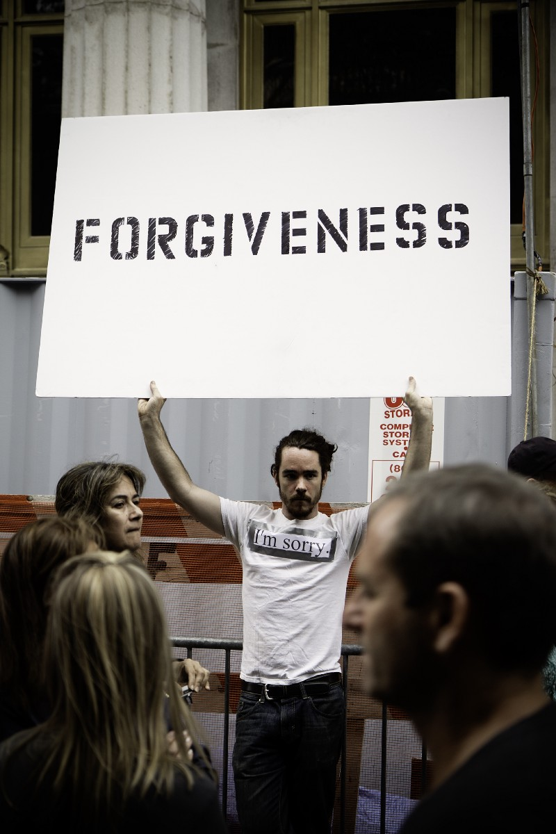 A man holding up a sign that says forgiveness