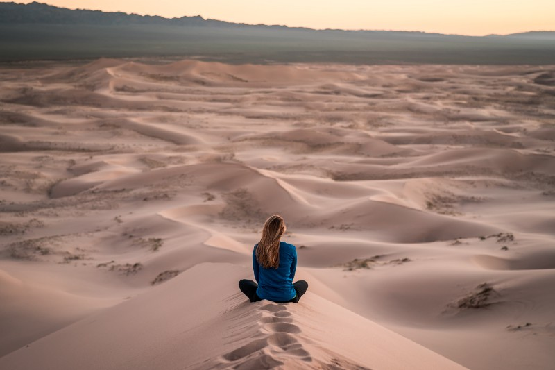 A woman sitting on a sand dune looking off into the distance.