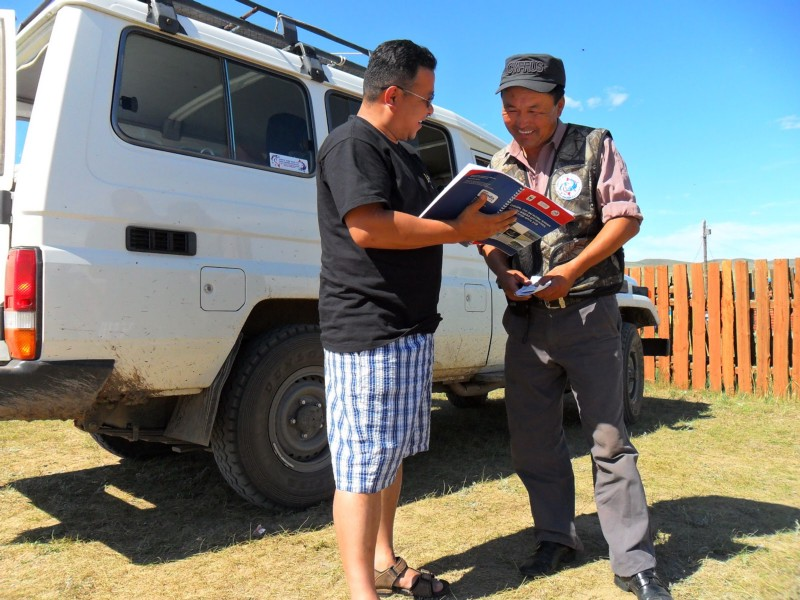 Local fisher sharing rule book with visitor in Mongolia