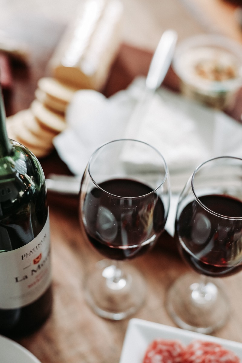 two glasses of red wine on a dinner table next to the bottle