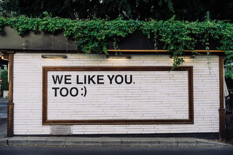 """""""We like you too"""" text on a wall. A very succinct piece of feedback."""