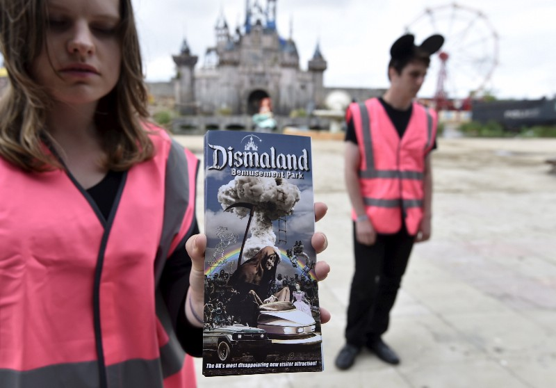 A performer holds a brochure for 'Dismaland', a theme park-styled art installation by British artist Banksy, at Weston-Super-Mare in southwest England