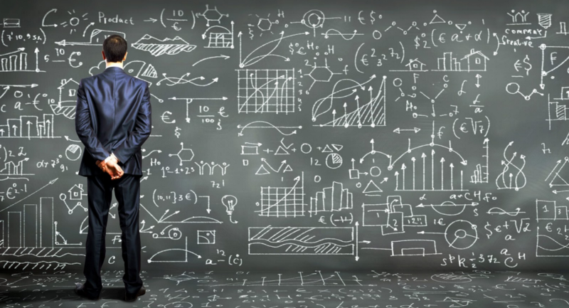 man looking at a blackboard with complex figures on it