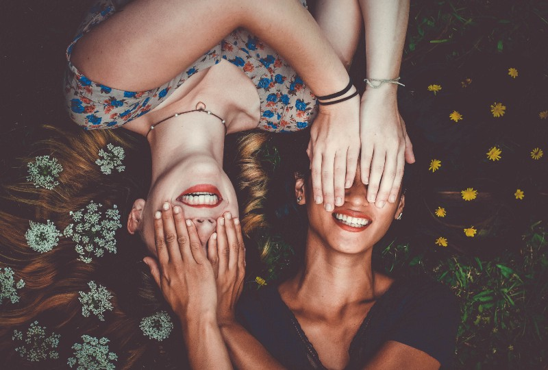 Two women laughing and covering each other's eyes.