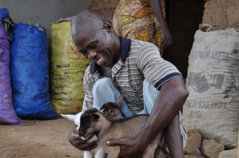A man sits on the ground, smiling, holding two small, brown baby goats. Behind him are large plastic and burlap bags traditionally found in African markets.