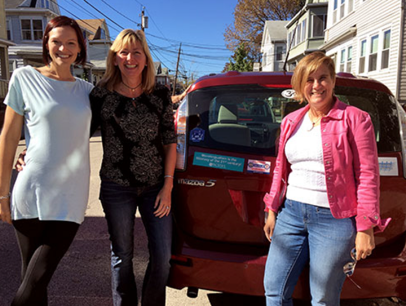 Three women standing in front of a red Mazda 5