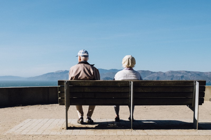 And older couple sit together on a park bench, slightly separated and looking in different directions.