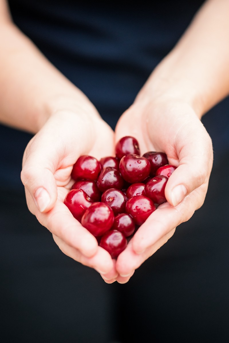 A woman with red cherries in her hand