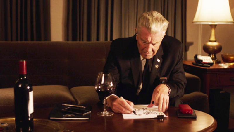 Gordon Cole draws with a glass of red wine in his hotel room
