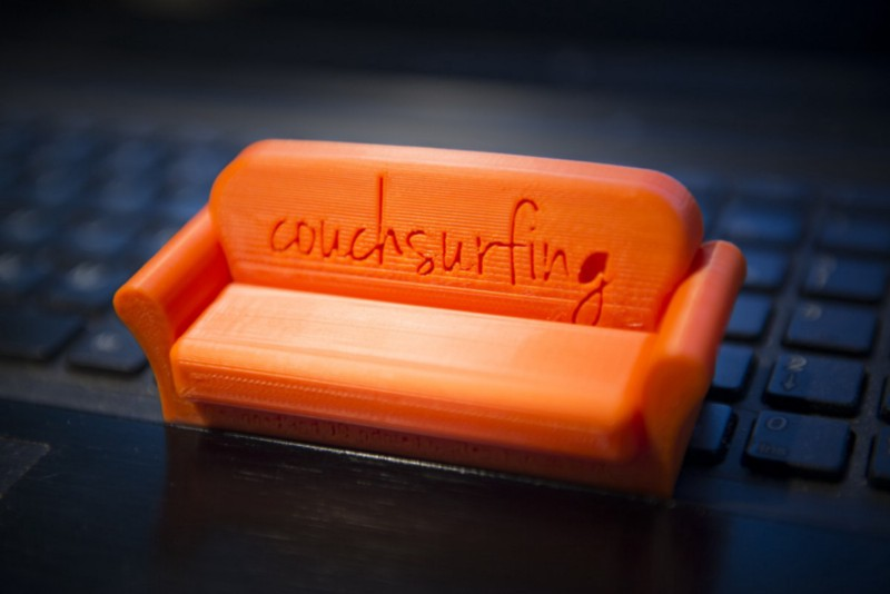 "orange model of a couch with ""couch surfing"" carved into the back"