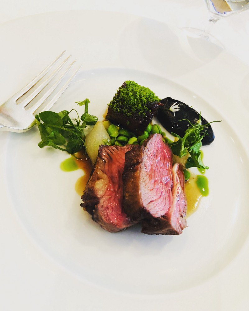 A dinner plate with medium rare steak and vegetables