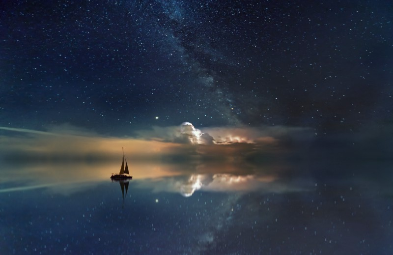 The silhouette of a sailing ship on a calm ocean at night