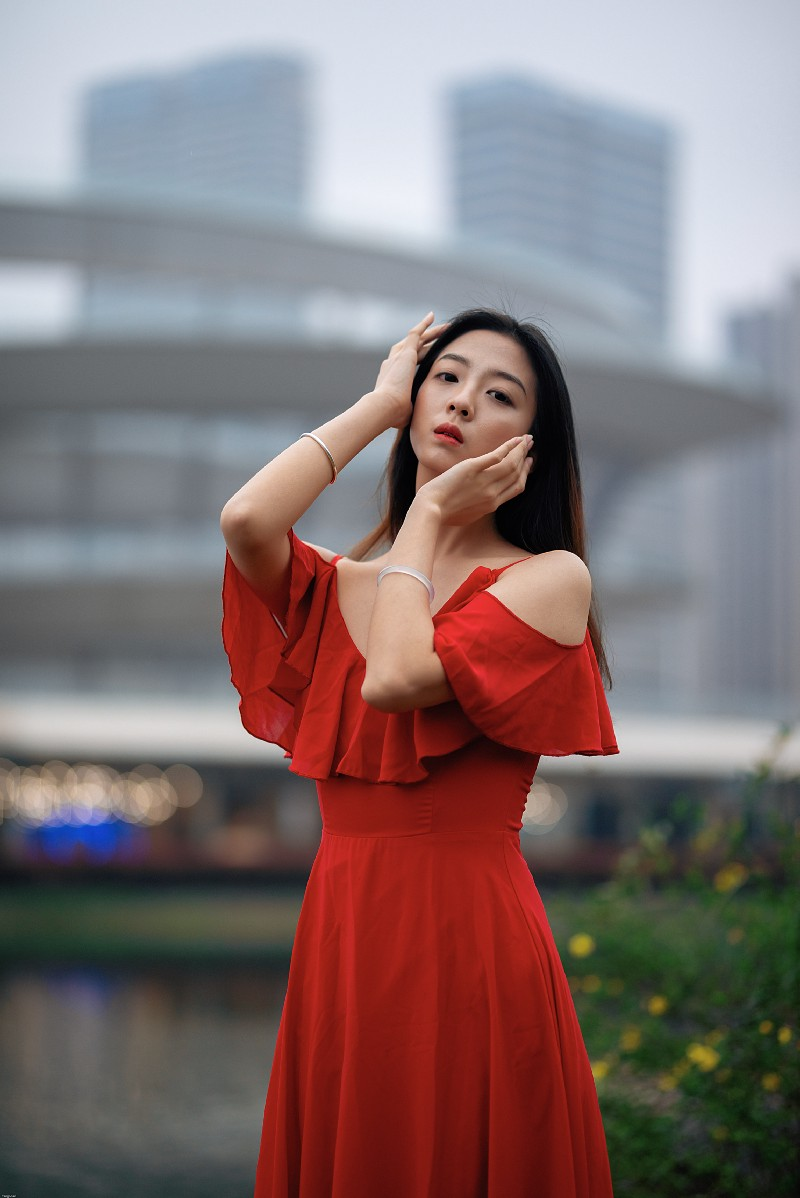 A Chinese woman in a red dress holds her face and looks at the camera.