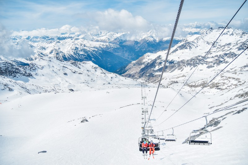 Cable car in the alps in wintertime. Skiiers moving up.
