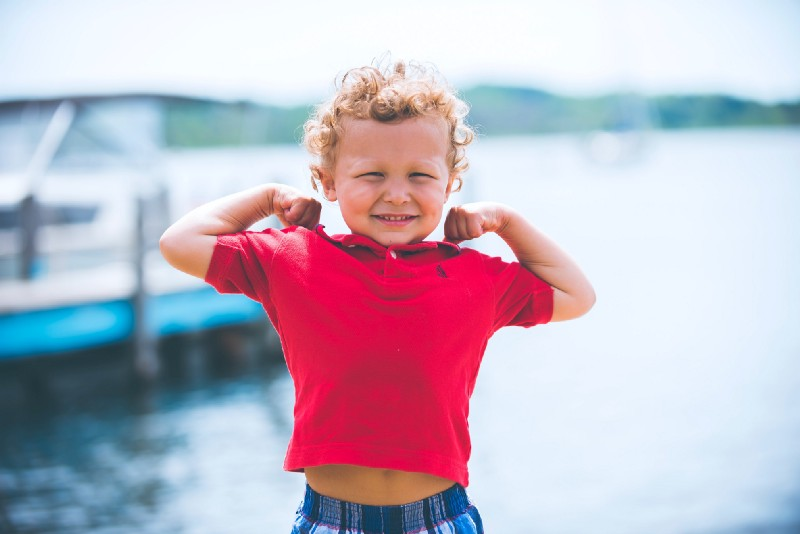 Toddler with curly blond hair wearing a red polo and flexing his arms. Water in the background.