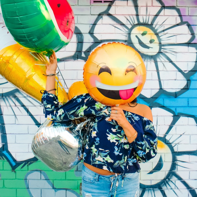Woman holding smiling emoji balloon in front of graffiti wall