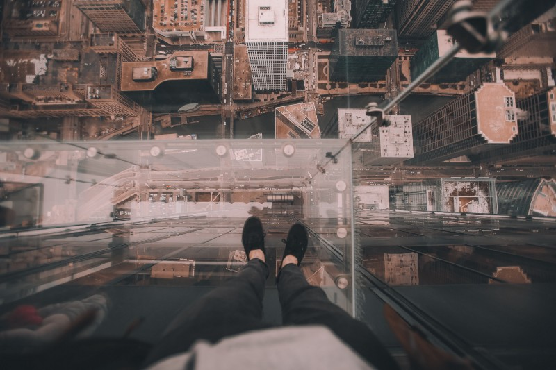 A person standing on a glass precipice on a tall building, looking down.