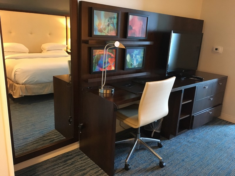 Full length mirror, desk, desk lamp, office chair, pictures hung, television
