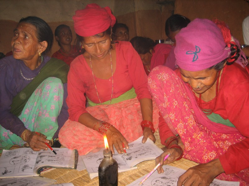 Three Nepali women sit on the floor writing in notebooks, in front of a candle.