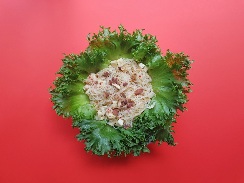 An Asian noodle salad served in a leafy green