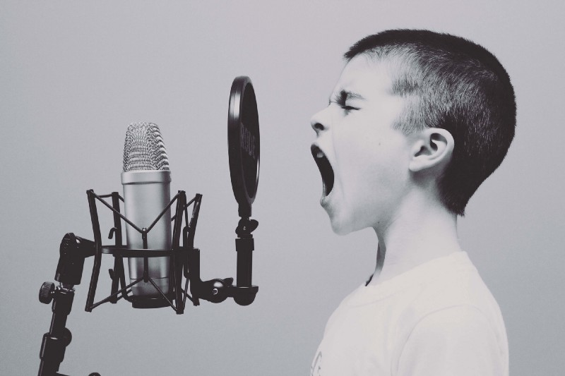 Black and white photo of boy screaming into a microphone
