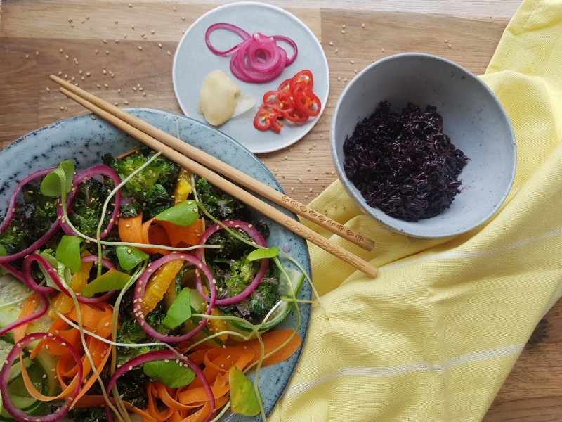 A bowl with flower sprouts and lots of colourful veggies, with chopsticks