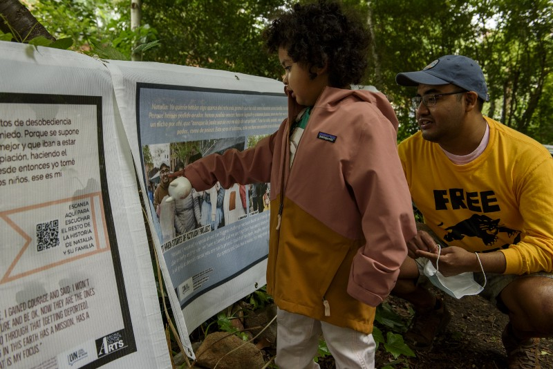 A child points to a picture of his father, on one of the banners hanging in the park