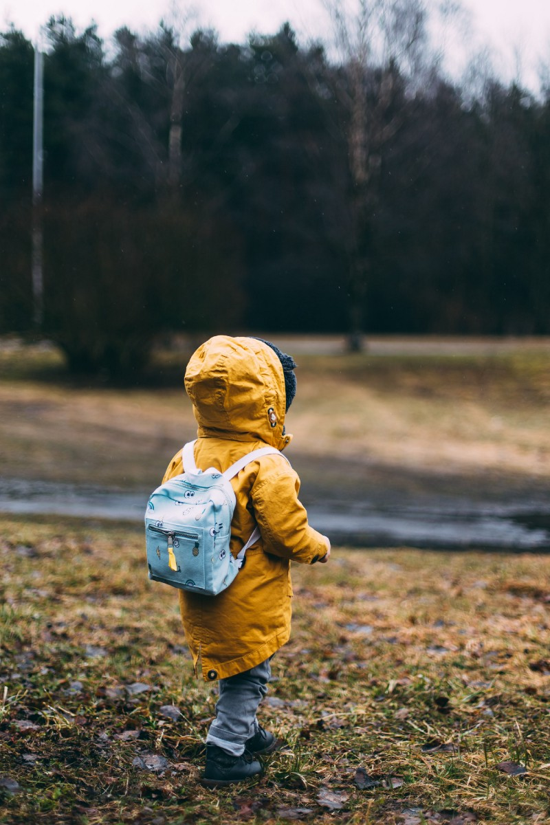 Photo of a child taken from behind. The child is wearing a rucksack and a yellow jacket. He's outdoors.
