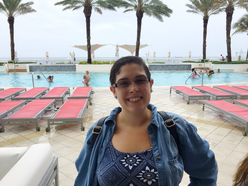 The outdoor pool of the Hilton Fort Lauderdale Beach with Ocean View in the background, palm trees, pool lounging chairs, hotel patrons in the pool, raining outside