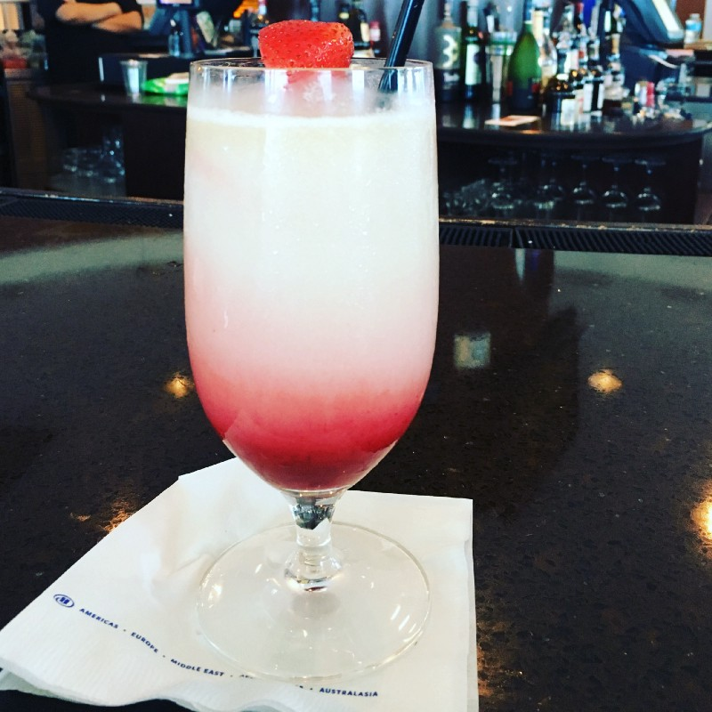 Pina colada with some strawberry flavor, strawberry garnish on the rim of the glass