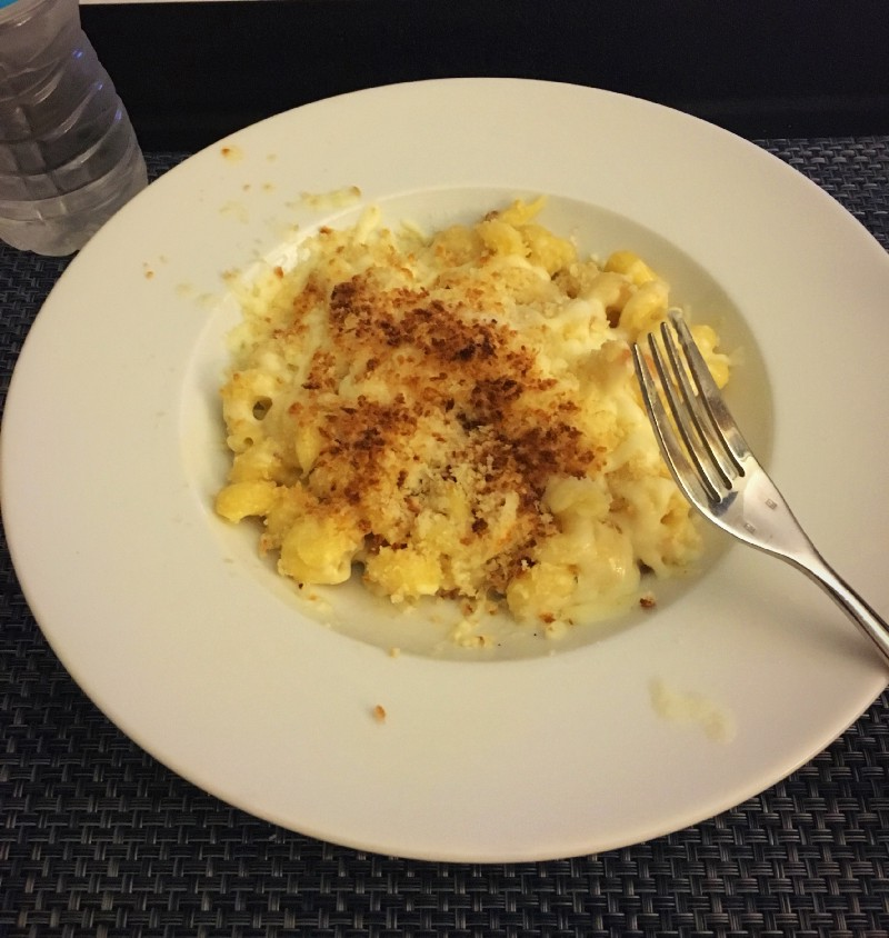 Bowl of Mac n Cheese with breadcrumbs on top, fork, water bottle