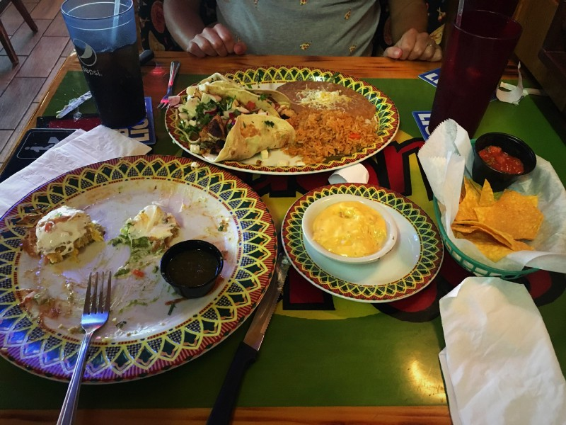 "Sweet Corn Cakes"" (left), our ""Rattle Snake Tacos"" (top middle), queso dip (bottom middle), and tortilla chips with salsa (right)."