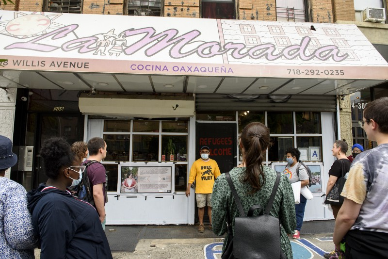 A group listens to a man in front of two banners, visible on the storefront of the restaurant La Morada