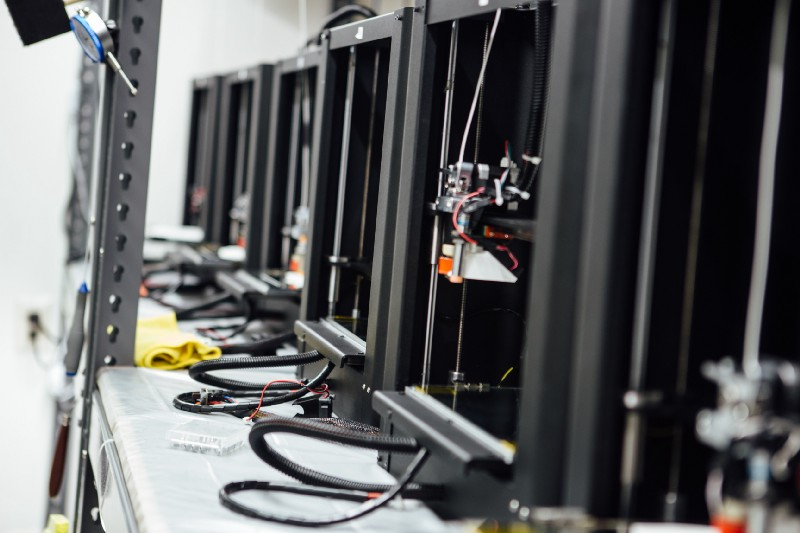 Image of a 3D printer farm from the side, sitting in a row